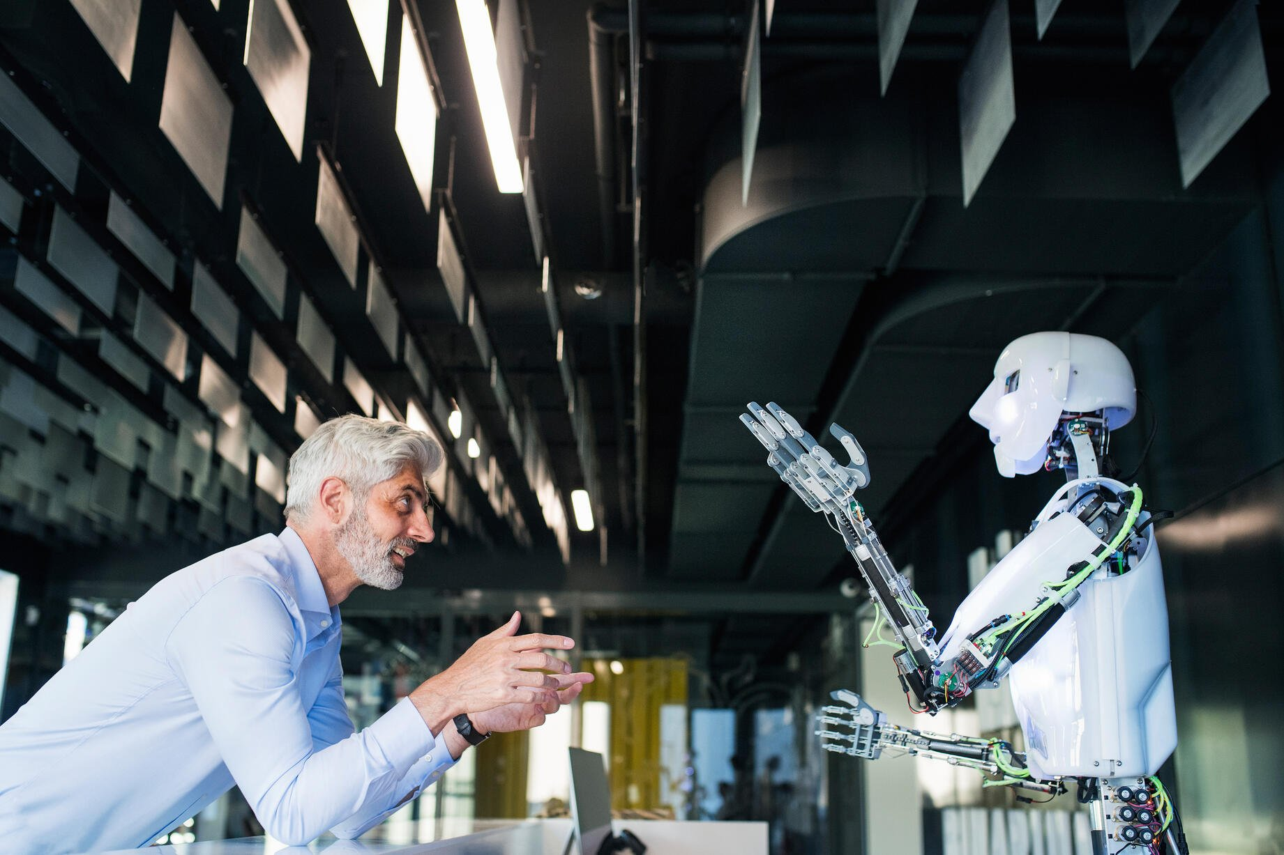 Businessman talks with white humanoid robot