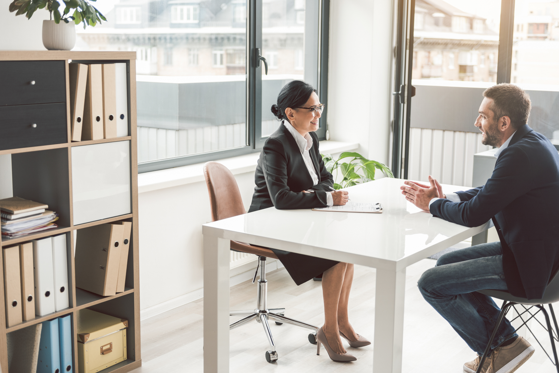Female boss and male employee chat at desk