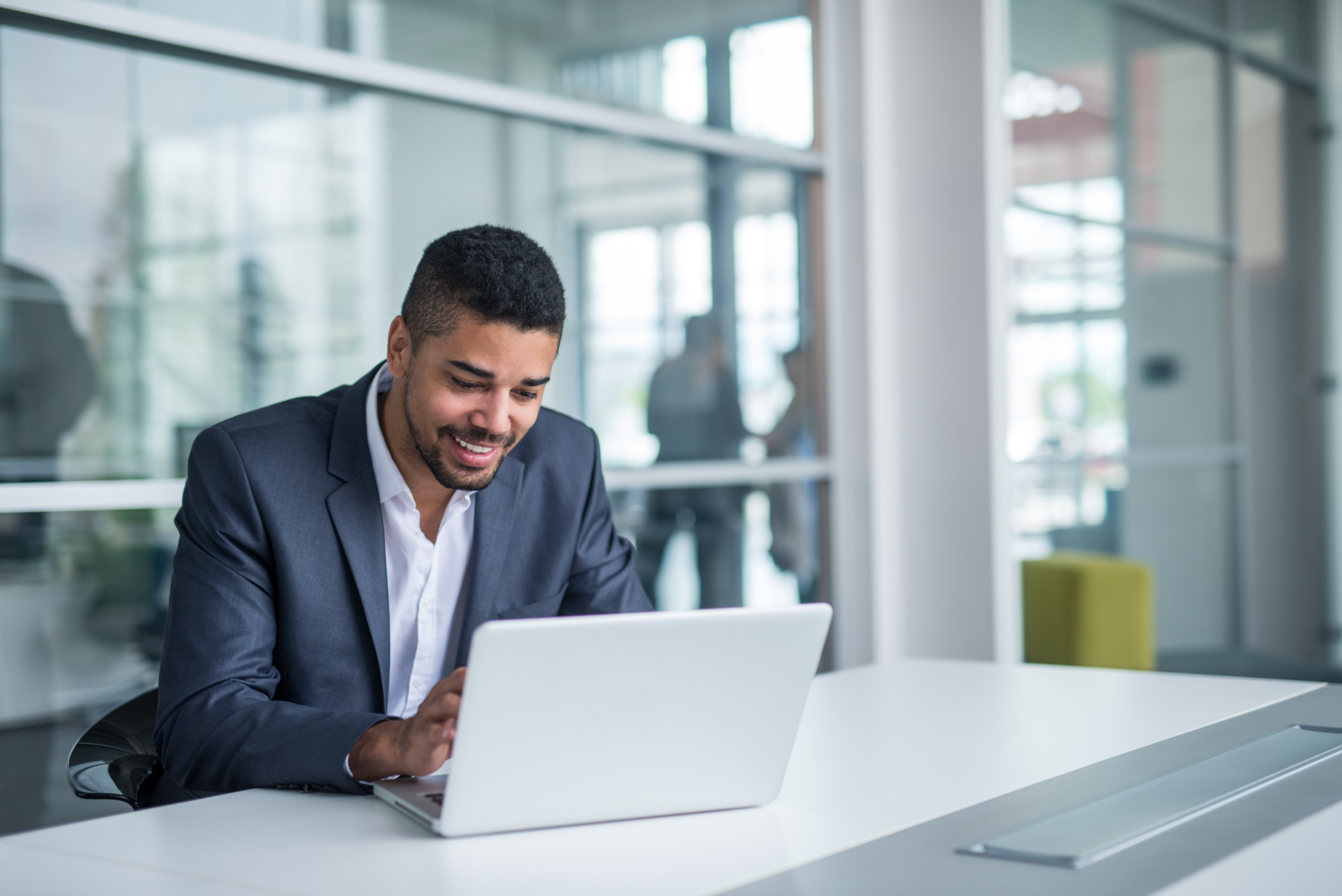 Young businessman uses laptop computer at work desk