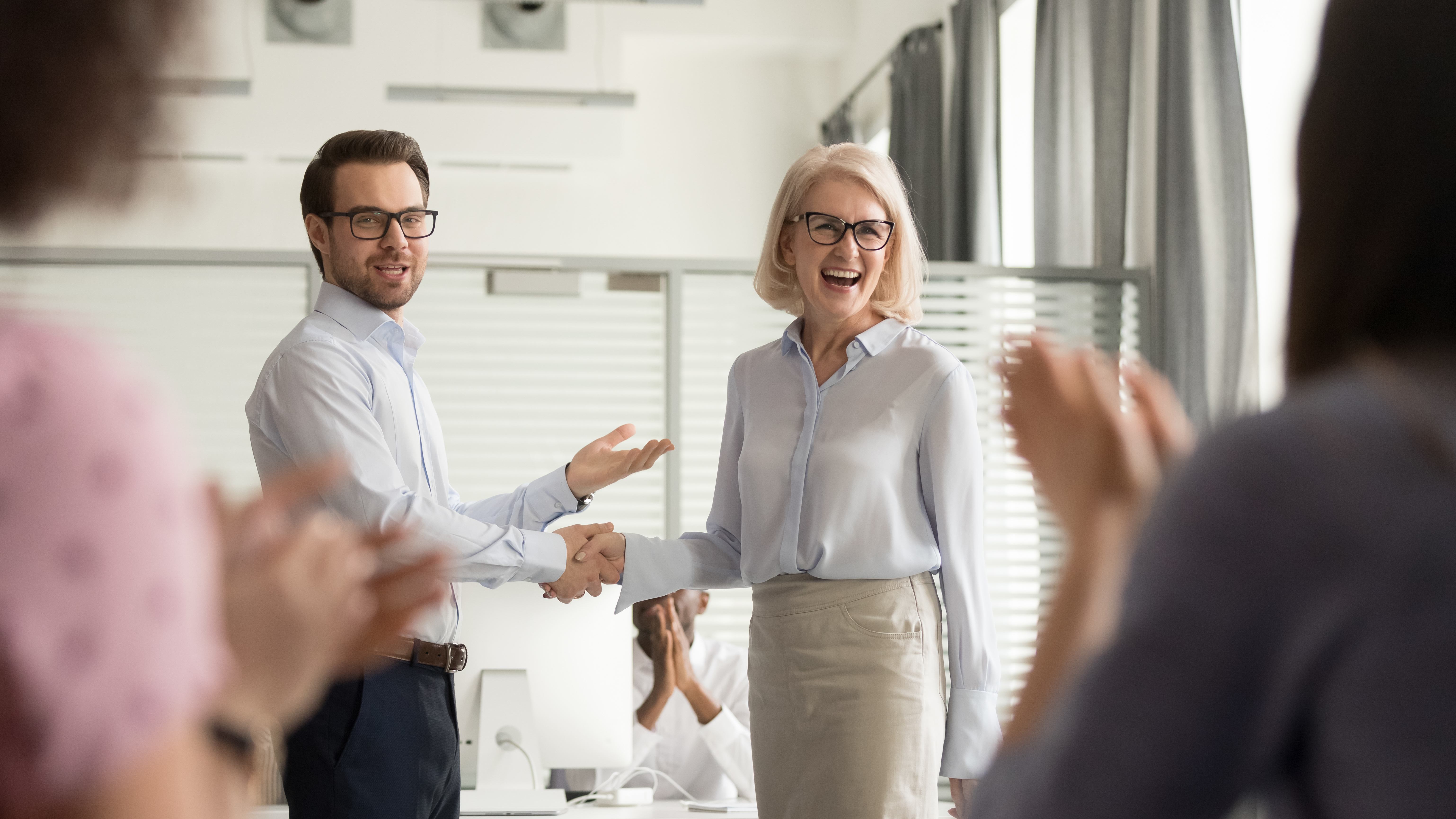 Businessman shakes hand of female coworker while employees clap